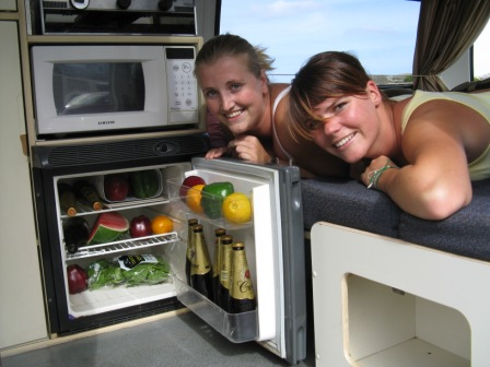 Photo of two girls inside Toyota Campervan by the fridge
