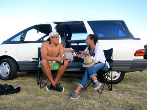Two travellers emjoying a beer outside of their used campervan for sale