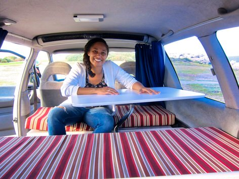 Maxime sitting at the table in the lounge of a 2 person used Toyota campervan